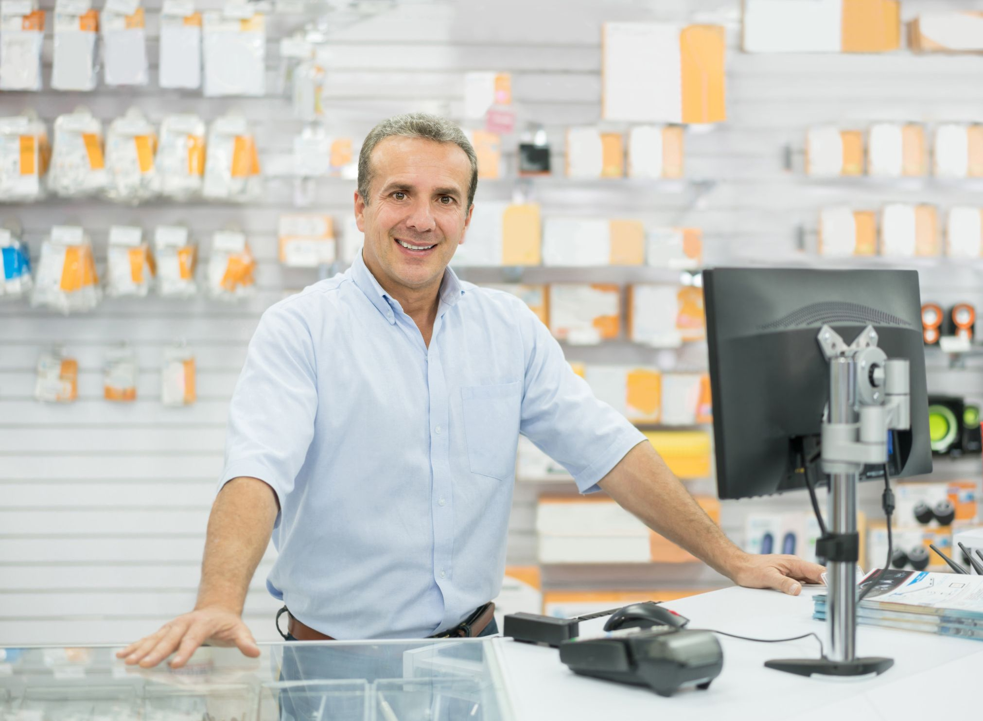 Casual man running an electronics store and smiling behind the counter